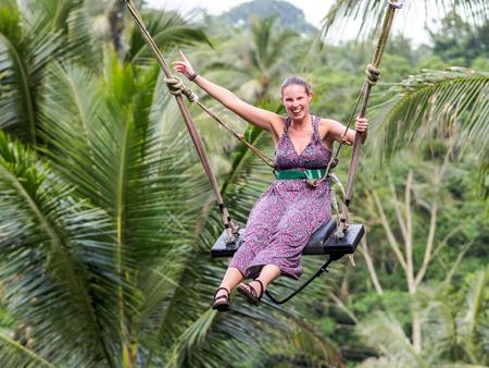 Caucasion woman having fun at Bali swing