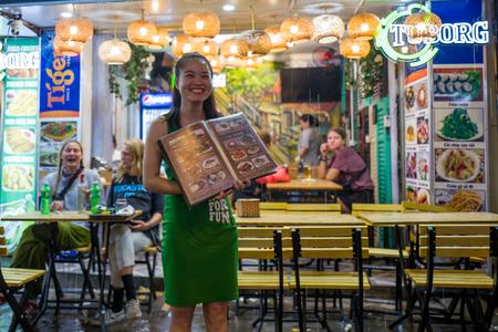 Hanoi, Vietnam - April 17, 2018: Waitress in the rain in Bia Hoi corner smiles at camera in Hanoi. Standard-Bild - 104685433