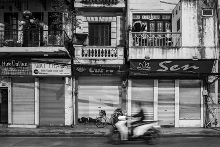 Hanoi, Vietnam - april 14, 2018: Scooter drives in front of sleeping man on the streets of Hanoi. Standard-Bild - 104685434