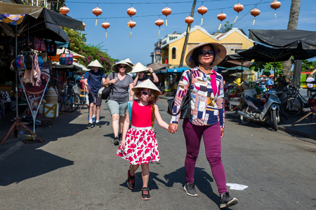 Hoi An, Vietnam - April 20, 2018: Tourists with traditional vietnamese hats walk down the old city of Hoi An. Standard-Bild - 104685438