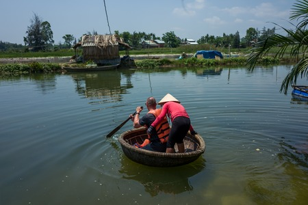 Caucasian man learns to use Thung Chai round boat with guide in Hoi An. Standard-Bild - 104685439