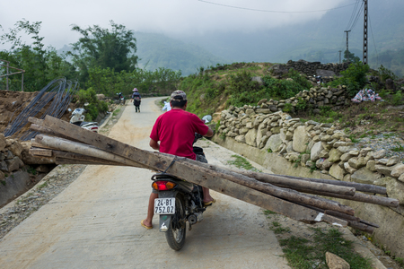 Sapa, Vietnam - April 24, 2018: Local man transports wood planks on scooter. Standard-Bild - 104685477