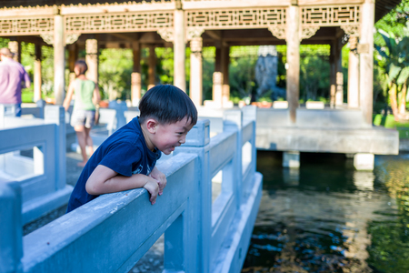Taipei, Taiwan - September 19, 2018: Kid looking at fish in the garden of the Palace Museum.