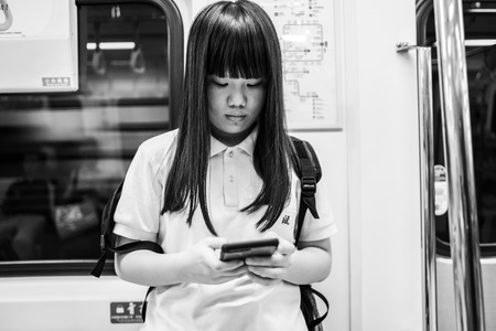 Taipei, Taiwan - October 01, 2018: A schoolgirl looking at her mobile phone in the Taipei MRT. Редакционное