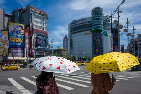 Taipei, Taiwan - September 18, 2018: Two girls with umbrellas protect themselves from the sun. Редакционное
