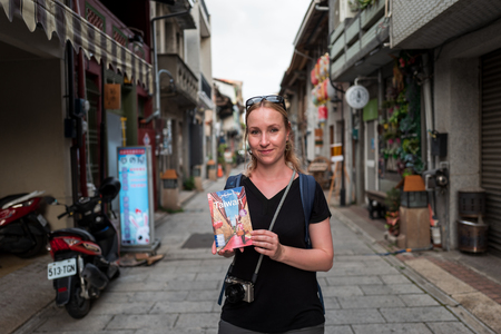 Tainan, Taiwan - September 25, 2018: Blonde girl holding Lonely Planet Travel Guide for Taiwan. Редакционное