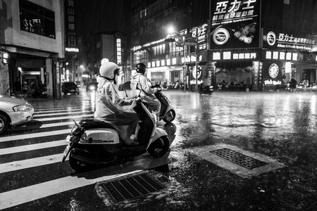 Tainan, Taiwan - September 25, 2018: People in the rain at night on the streets of Tainan.
