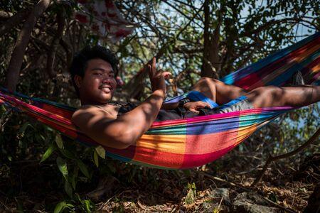 Ko Adang, Thailand - February 19, 2019: Local man in hammock smiling at camera.