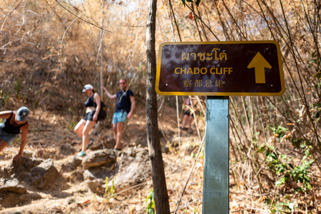 Chado Cliff sign with people walking in background on Ko Adang, Thailand