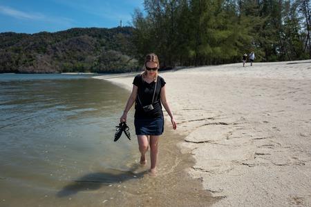 Blonde caucasian girl walking at a beach in Kilim Karst Geoforest Park in Langkawi, Malaysia.