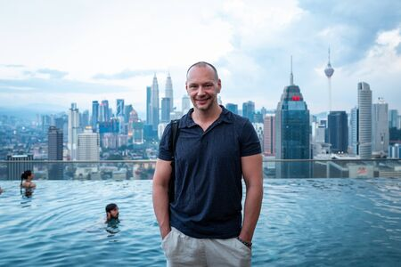 Kuala Lumpur, Malaysia - February 27, 2019: Caucasian man with view to the skyline with Petronas Towers from Infinity Pool.