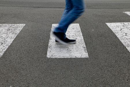 paso de peatones: In the street, a man crossing a crosswalk