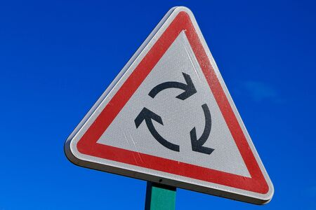 roundabout: roundabout road sign on blue sky Stock Photo