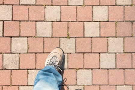 paved: a man walk on the paved sidewalk in the street
