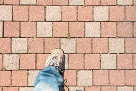 empedrado: un hombre de pie en la acera pavimentada en la calle