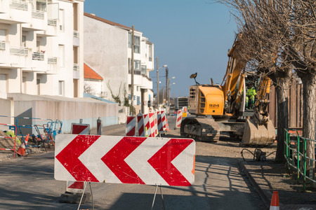 trenching: Saint Gilles Croix de Vie, France - March 31, 2016 : during roadworks, a man uses excavating machine for trenching operation Editorial