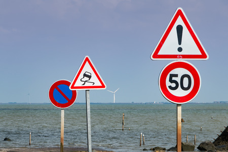no skid: together of road signs for warning next to sea