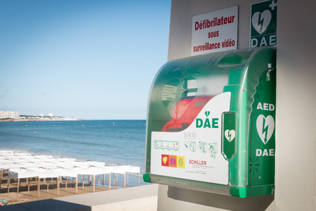 bitch: Sables-d-Olonnes, France - July 05, 2016 : AED - public automatic defibrillator on the bitch with french sign : defibrillator with video control