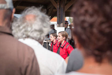 fanfare: Saint Gilles Croix de Vie, France - July 14, 2016 : Public rear view looking to play a marching band on the street with her dancing girl during the the French National Day
