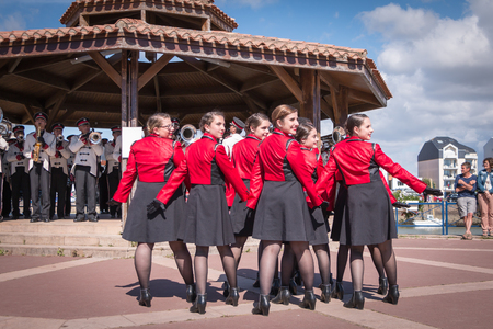 fanfare: Saint Gilles Croix de Vie, France - July 14, 2016 : set of dancers accompanying a fanfare at the French National Day