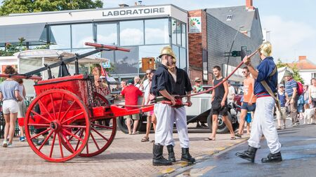 plunges: Challans, France - August 11, 2016 : event Once Challans Autrefois Challans organized by the city and plunges visitors into the city from the early 20th century - Firefighters have an antique pump early 20th century