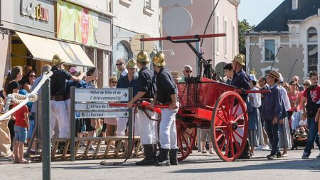 intervene: Challans, France - August 11, 2016 : event Once Challans Autrefois Challans organized by the city and plunges visitors into the city from the early 20th century - antique firefighters to intervene with a water pump