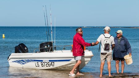 returning: Bretignolles sur Mer, France - August 14, 2016 : regional angling trust sea competition - men returning from a sea fishing competition