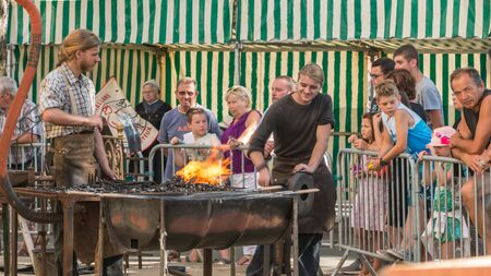 plunges: Challans, France - August 11, 2016 : event Once Challans Autrefois Challans organized by the city and plunges visitors into the city from the early 20th century - demonstration by two blacksmiths labor metal to the old way