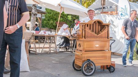plunges: Challans, France - August 11, 2016 : event Once Challans Autrefois Challans organized by the city and plunges visitors into the city from the early 20th century - man plays the barrel organ in the street Editorial