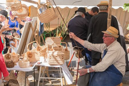 plunges: Challans, France - August 11, 2016 : event Once Challans Autrefois Challans organized by the city and plunges visitors into the city from the early 20th century - man sells wicker baskets on a market Editorial