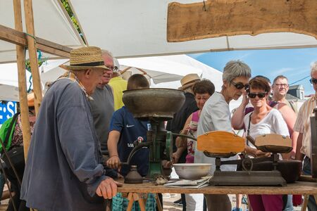 plunges: Challans, France - August 11, 2016 : event Once Challans Autrefois Challans organized by the city and plunges visitors into the city from the early 20th century - an old man operates an ancient machine to grind grain