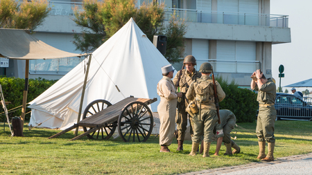 reconstituted: Les Sables dOlonne, France - August 26, 2016 : commemoration of the Liberation of Les Sables dOlonne, which took place on the night of August 27 to 28, 1944 - French and American soldiers relaxing in a reconstituted military camp