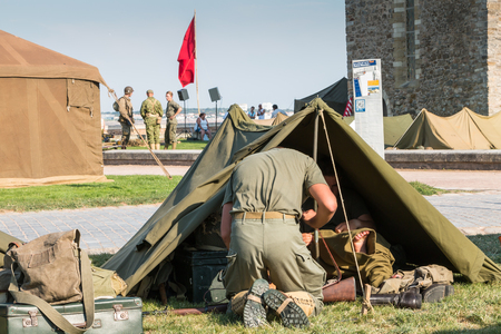 45 gun: Les Sables dOlonne, France - August 26, 2016 : commemoration of the Liberation of Les Sables dOlonne, which took place on the night of August 27 to 28, 1944 - American soldiers sit in their tent tactics