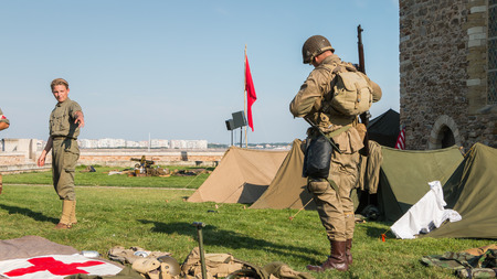 reconstituted: Les Sables dOlonne, France - August 26, 2016 : commemoration of the Liberation of Les Sables dOlonne, which took place on the night of August 27 to 28, 1944 - US soldiers stand guard in a reconstituted military camp Editorial