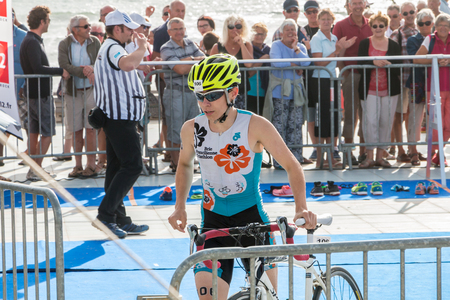 Saint Gilles Croix de Vie, France - September 10, 2016 : Final triathlon championship of France in the category D3 - athlete running with his bike to the bike course