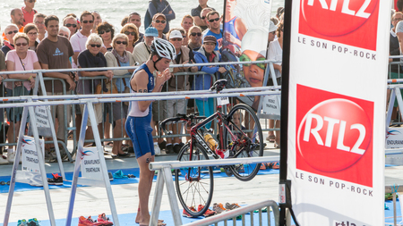 exiting: Saint Gilles Croix de Vie, France - September 10, 2016 : Final triathlon championship of France in the category D3 - after exiting the water, athletes take their racing bike Editorial