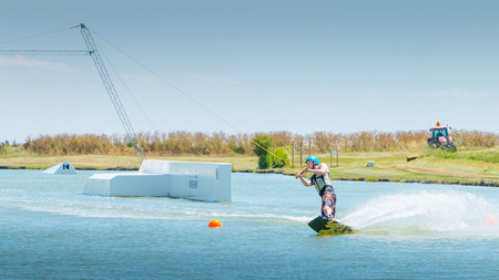 Aiguillon-sur-Mer, France, France - July 06, 2016 : installing a wake park during the 2016 season on the Lake of Aiguillon sur Mer, France - wakeboarder is exerted on the lake to make figures