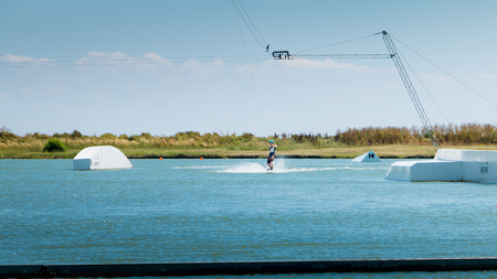 exerted: Aiguillon-sur-Mer, France, France - July 06, 2016 : installing a wake park during the 2016 season on the Lake of Aiguillon sur Mer, France - wakeboarder is exerted on the lake to make figures