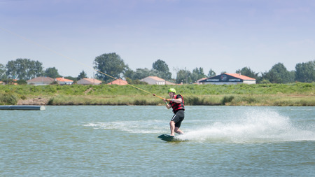 Aiguillon-sur-Mer, France, France - July 06, 2016: Installing a wake park During the 2016 season on the Lake of Aiguillon sur Mer, France - wakeboarder is exerted on the lake to make figures
