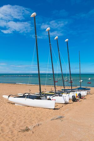 Four catamarans laid on the sand by the sea in France