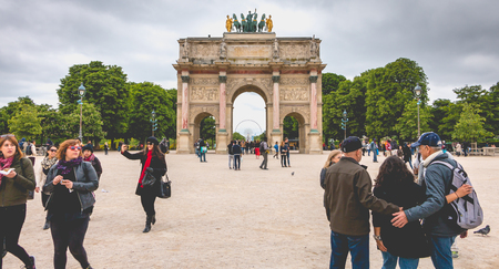 Paris, France - May 08, 2017 : In the garden of the tuileries, tourists walk before the triumphal arch of the carousel. The arch was built from 1806 to 1808 to commemorate the Napoleons military victories