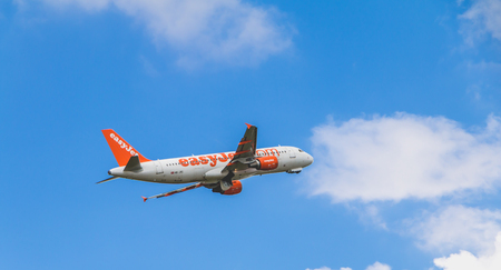 Nantes, FRANCE - April 27, 2017 ; Airbus A320-214 of EasyJet registered HB-JXC flying above Nantes Atlantique Airport with clouds background Editorial