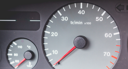 visible: Old car dashboard of the 90s with speedometer, tachometer, fuel gauge and temperature control