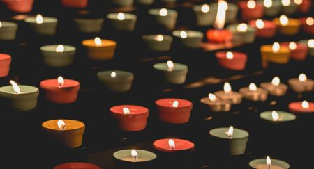 Many candle flames glowing in the dark, create a spiritual atmosphere Stock Photo