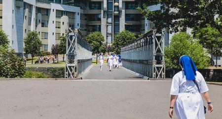 religious habit: Lourdes, FRANCE, June 22, 2017 - sisters walk in the gardens of the sanctuary of Lourdes, France