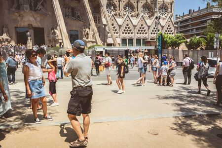 BARCELONA, SPAIN - June 21, 2017 : tourists making pictures in front of the Sagrada Familia, a wide Roman Catholic church designed by Catalan architect Antoni Gaudi Редакционное
