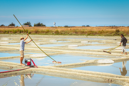 NOIRMOUTIER, FRANCE - July 03, 2017 : Two men harvest salt in the traditional way in the salt marshes of Noirmoutier, france