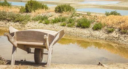 salinity: wooden wheelbarrow in front of salt marshes in Noirmoutier, France Editorial