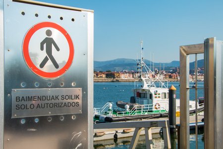 BILBAO, SPAIN - July 18, 2016 : at the entrance of a landing stage a sign prohibits access to pedestrians with a text in Spanish and Basque which says only authorized