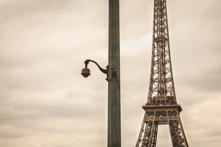 private security: black security camera on a pillar in bad weather in front of the Eiffel Tower in Paris, France